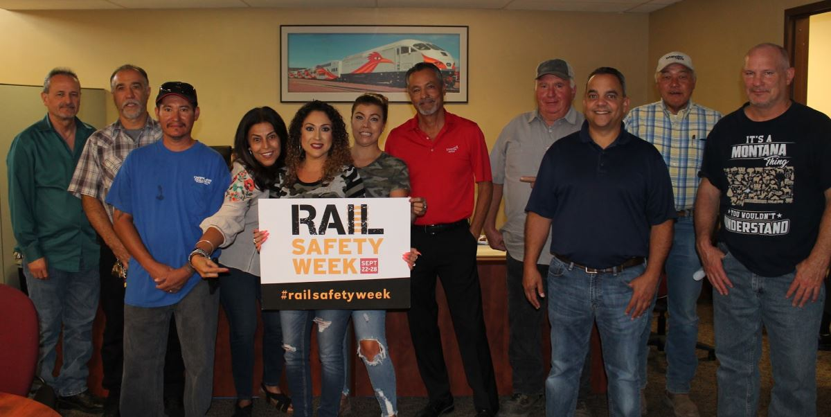 Rail operations staff holding rail safety sign