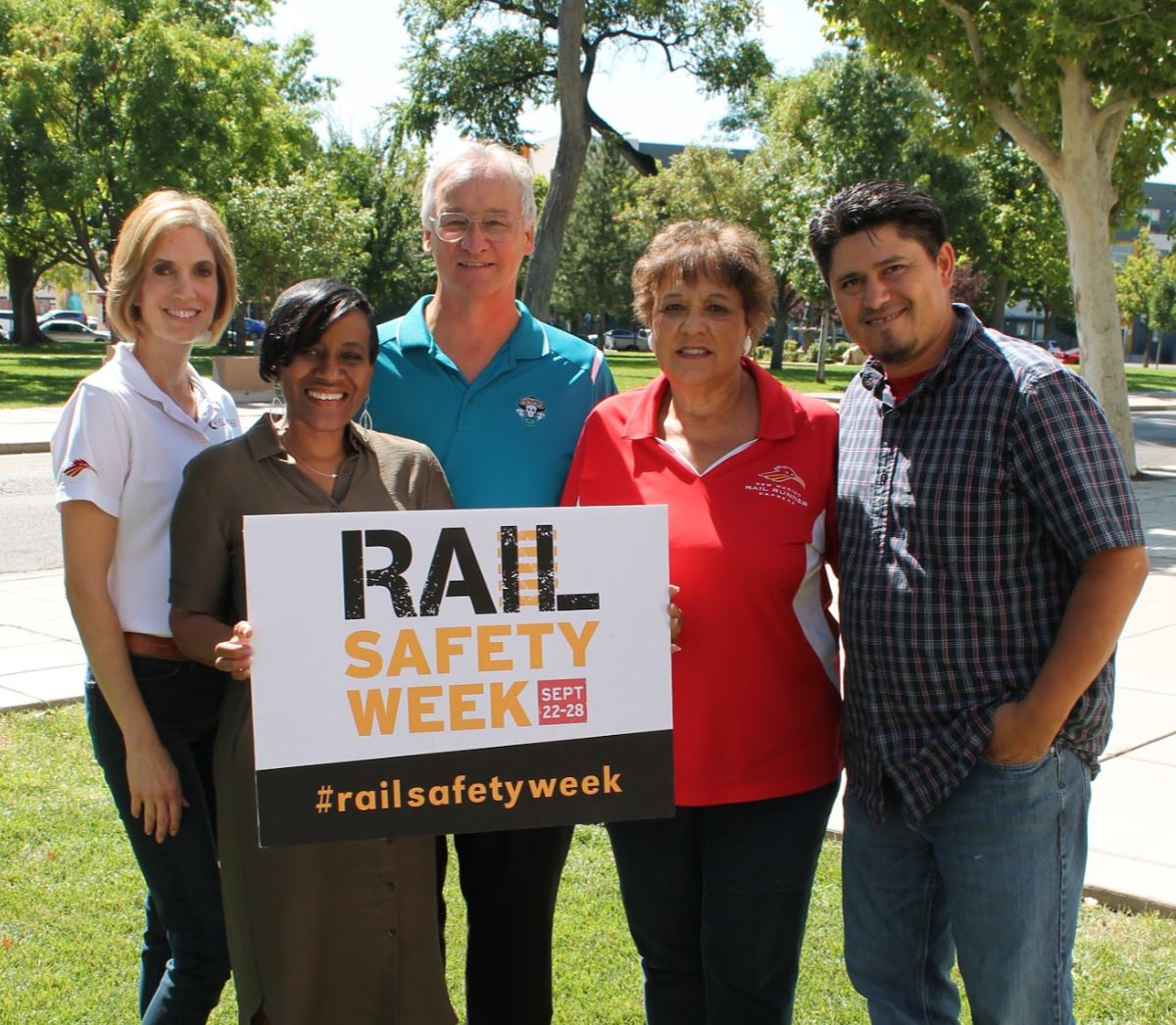 Marketing staff holding rail safety sign