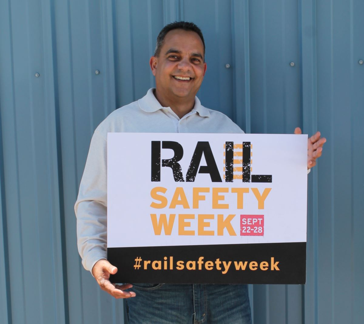 Gil Melgarejo holding rail safety sign